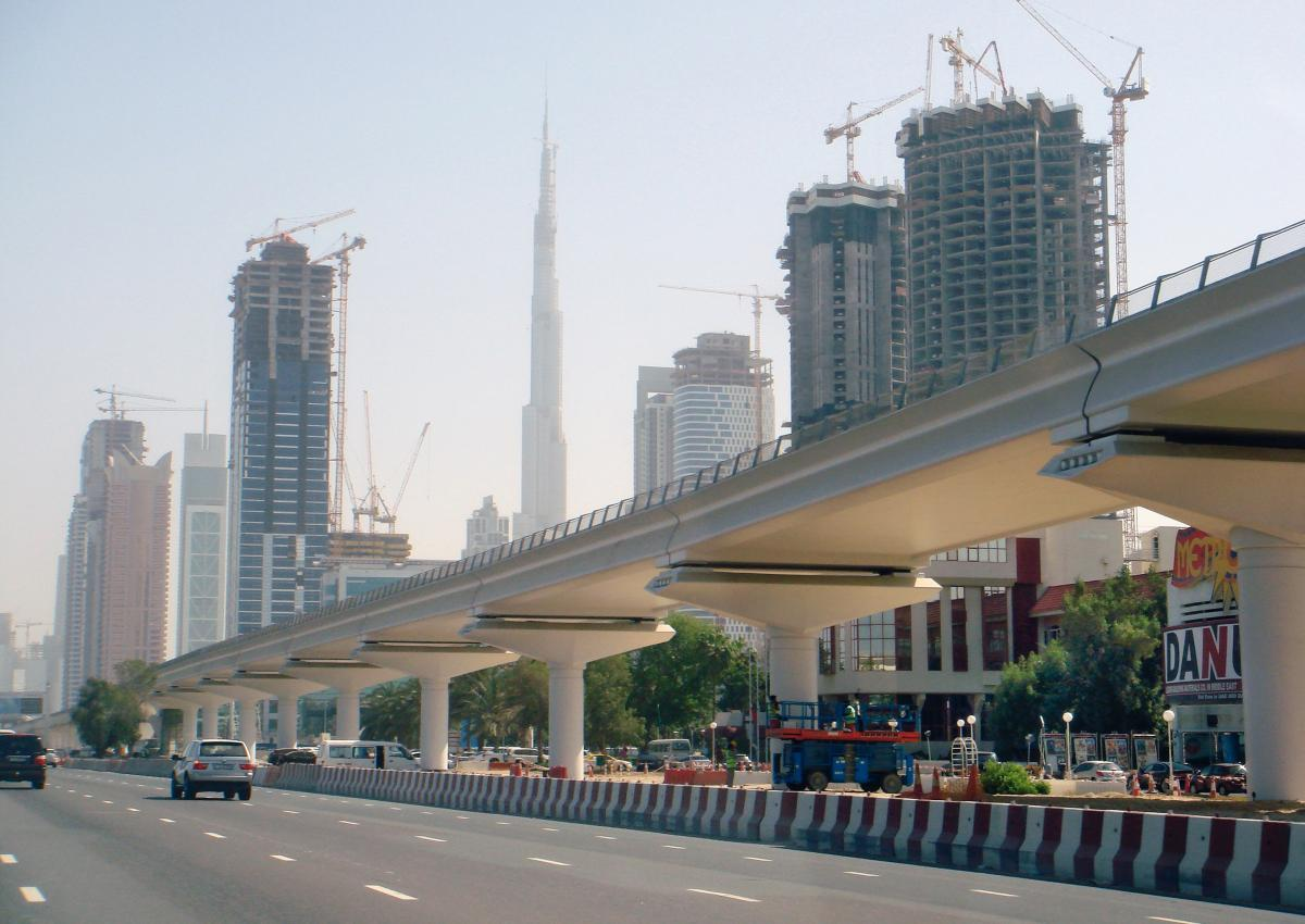 Along the main street of the new Dubai, an elevated track of the Metro is being constructed. In the background, the tallest building in the world reaches for the most often hazy skies: Burj Dubai.
